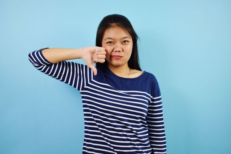 Portrait of young woman standing against blue background