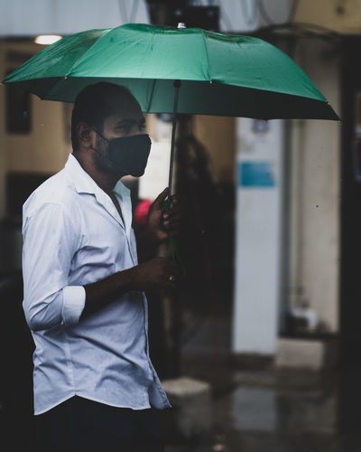 Midsection of man holding umbrella standing in rainy season
