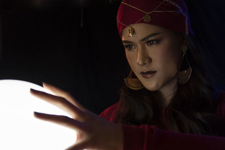 Female fortune teller with sphere against black background