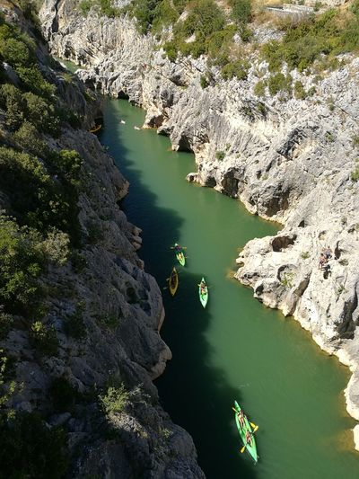 High Angle View Of People On Canoeing In River Amidst Rock Formations