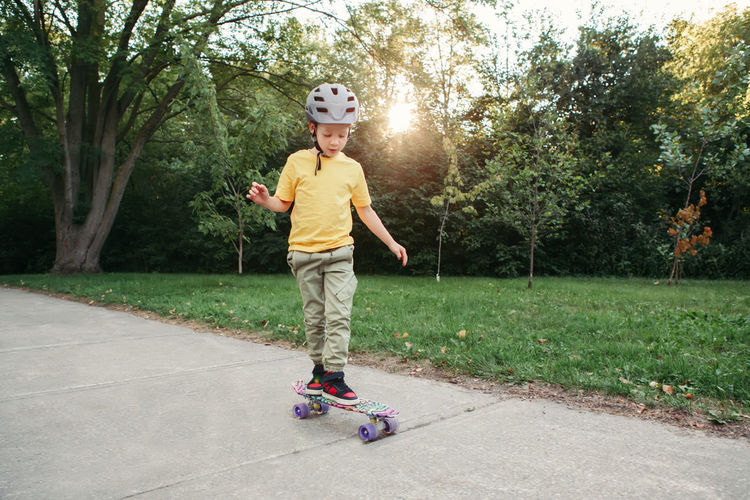 Boy in grey helmet riding skateboard in park on summer day. seasonal outdoor children activity