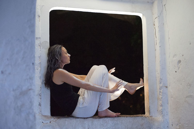 Woman covered with paint sitting on window sill at night