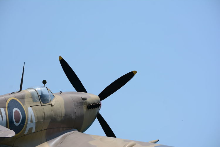 Low angle view of fighter plane against clear blue sky