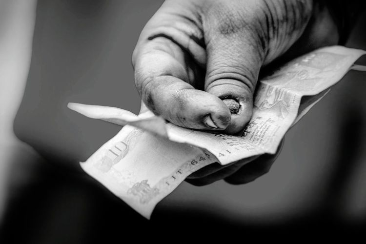 Cropped Image Of Poor Man Holding Indian Currency