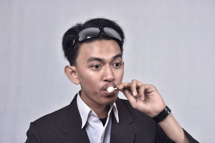 Man Sucking Lollipop Against Gray Background