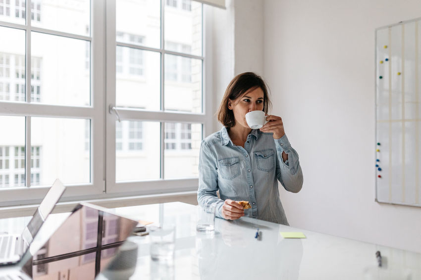 Adults Only Break Business Coffee Cookie Day Drinking Coffee Holding Indoors  Meeting Meeting Room Occupation Office One Person Only Women Real People Snacking Standing Table Technology White Window Women Working Young Women