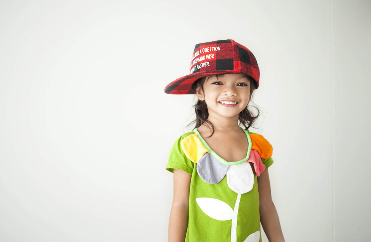 childhood, looking at camera, children only, child, girls, standing, studio shot, smiling, red, portrait, cap, happiness, white background, one person, day, people, adult