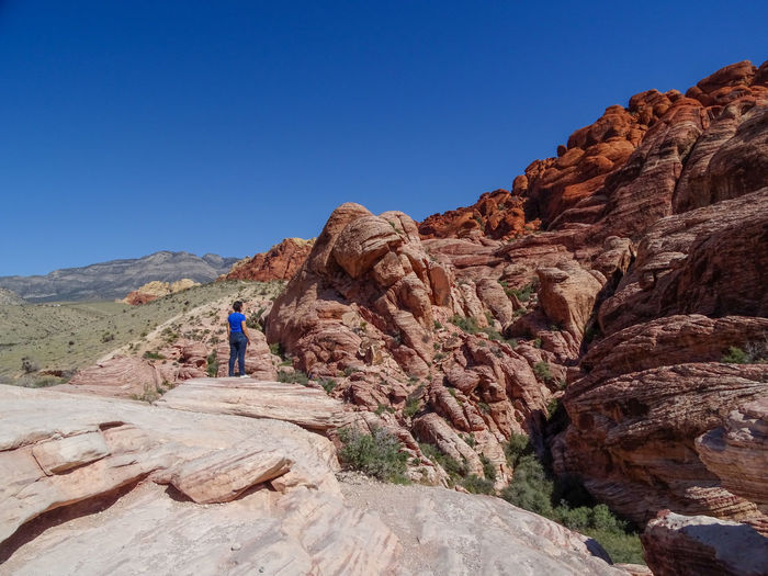 Man on rock formation against clear blue sky
