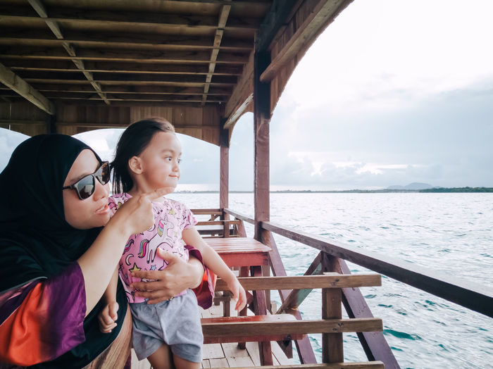 Mother with daughter looking at view from boat