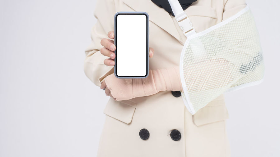 Midsection of person holding smart phone against white background