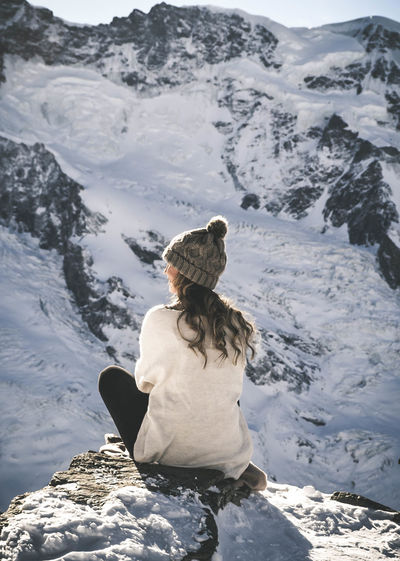 Rear View Of Woman Sitting On Cliff During Winter