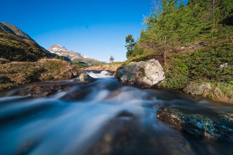 River flowing through rocks against sky