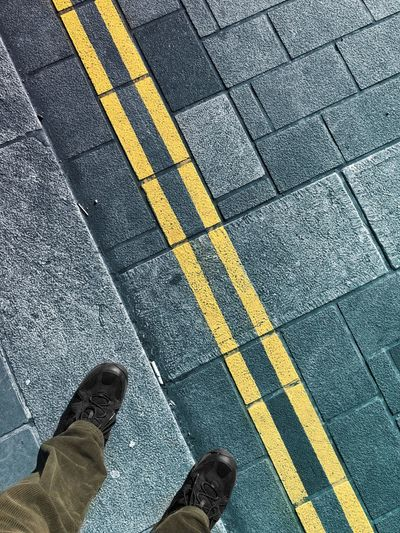 Low section of person standing on road