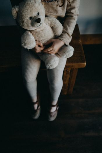 Low section of girl with stuffed toy sitting on table at home