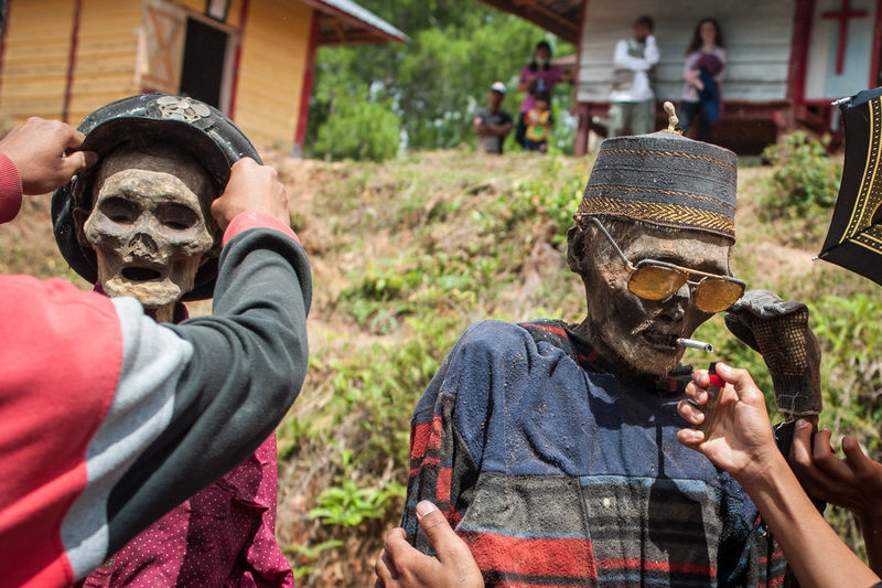 Manene ritual in Indonesia. Adult Architecture Casual Clothing Clothing Day Friendship Hat Headshot Holding Leisure Activity Lifestyles Men Obscured Face Outdoors People Portrait Real People Waist Up
