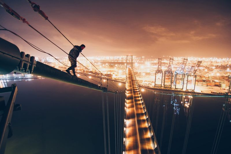 Man Standing On Steel Cable Of Suspension Bridge Over River By Harbor At Night