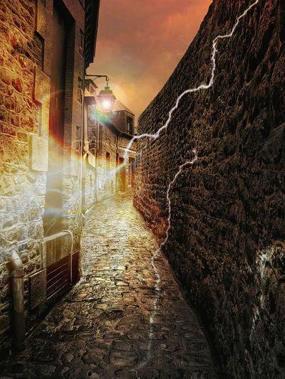 Walkway amidst illuminated buildings against sky