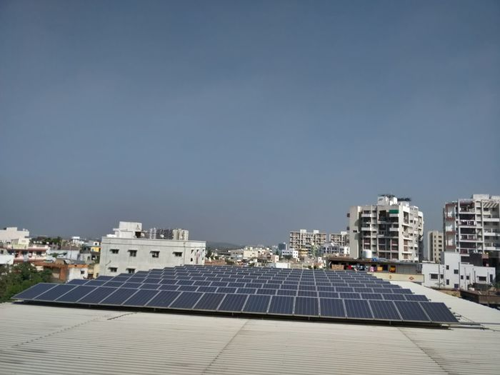 Scenic view of solar panels on buildings against clear sky