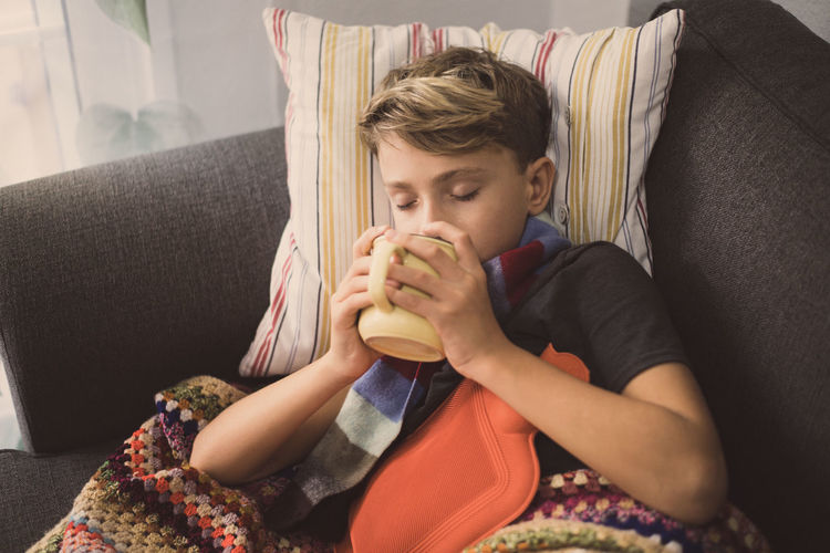 Ill boy with hot water bottle lying on sofa while drinking coffee