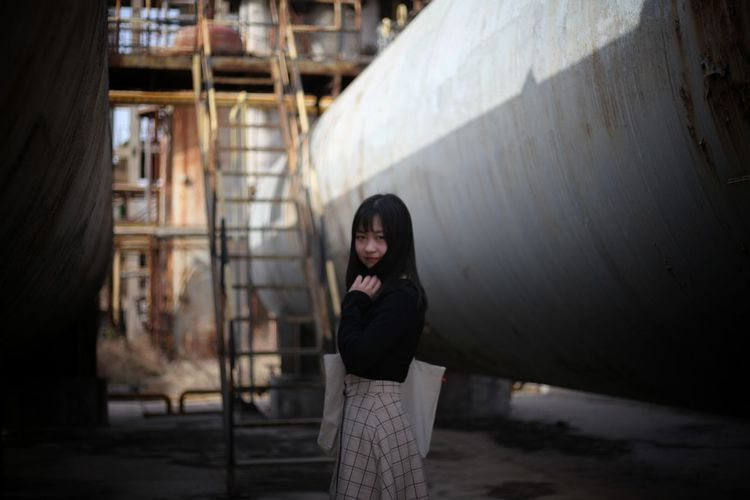 Portrait of young woman standing by pipe at industry