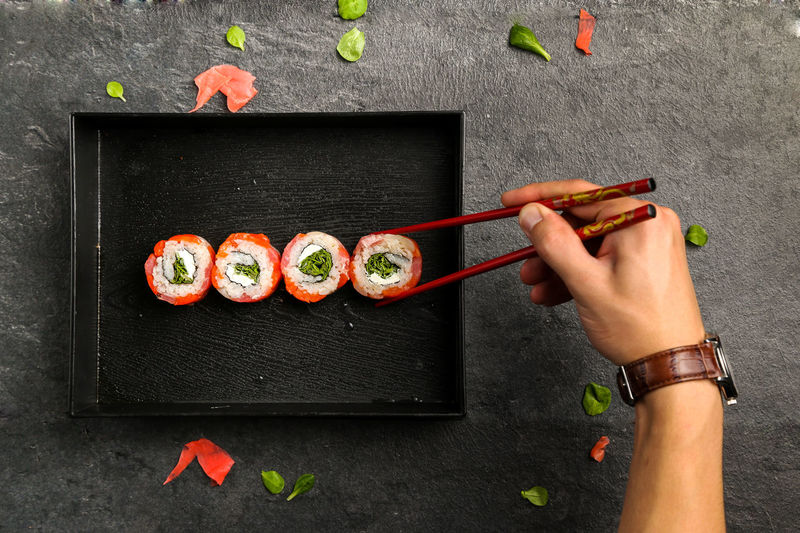 Cropped Image Of Man Holding Sushi With Chopsticks In Plate
