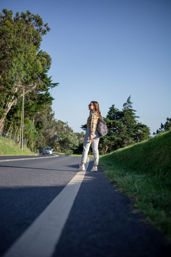 Woman walking on road amidst trees against sky