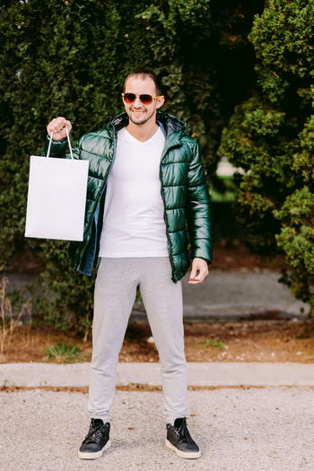 Portrait of man wearing sunglasses holding bag standing outdoors