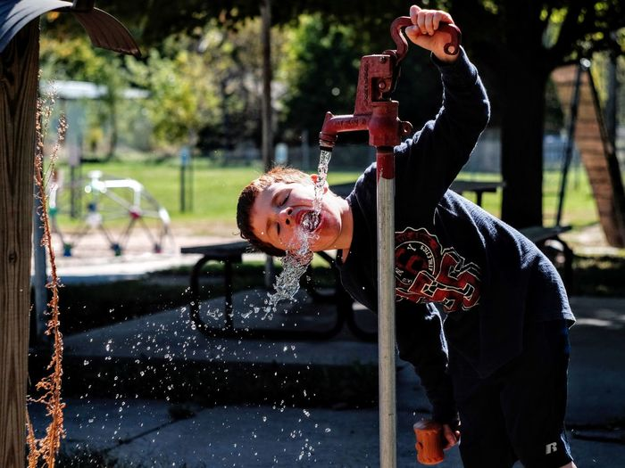 Boy Drinking Water From Tap In Park