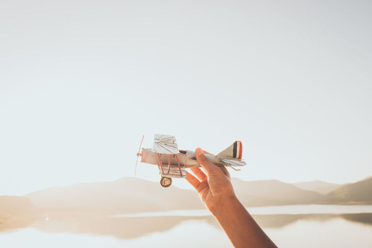 Low angle view of hand holding toy airplane against clear sky