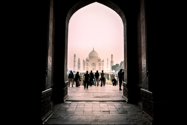 People And Taj Mahal Seen Through Arch Against Sky