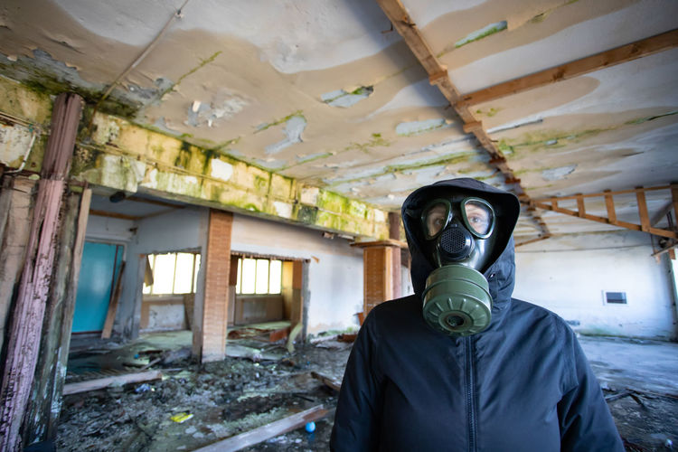 Portrait of man standing in abandoned building