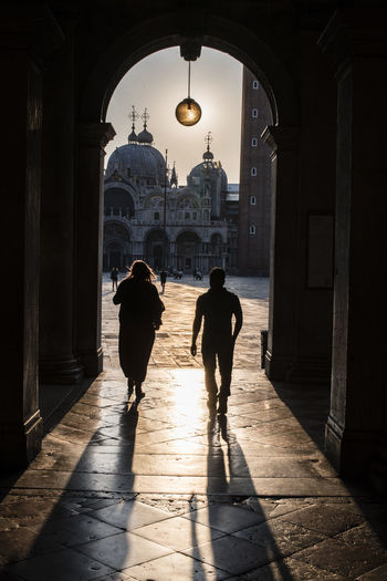 Rear View Of Man And Woman Walking In Archway
