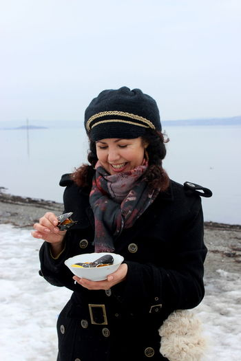 Woman Eating Seafood Against Lake During Winter
