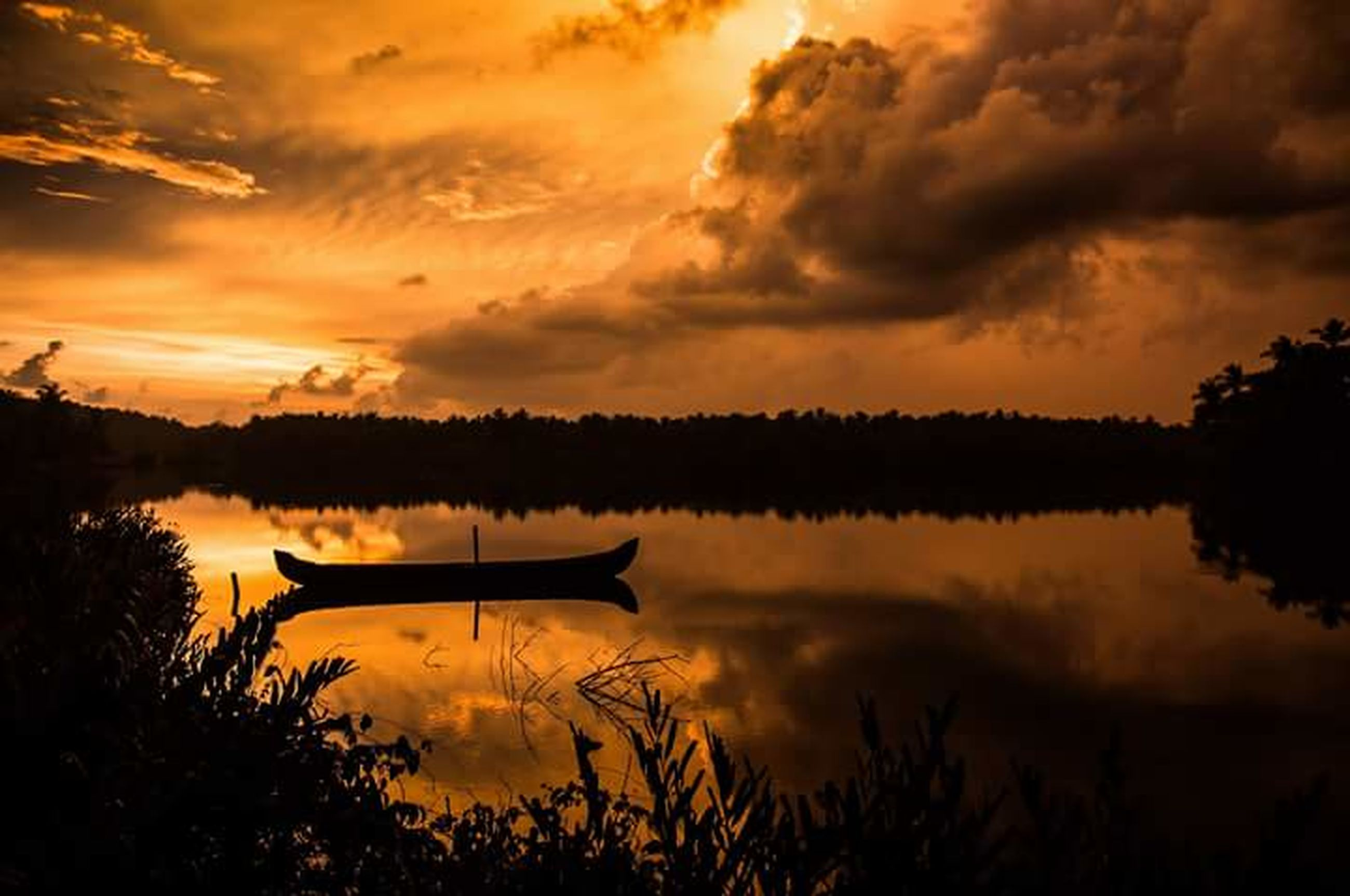 sunset, water, sky, reflection, lake, tranquility, cloud - sky, tranquil scene, silhouette, scenics, beauty in nature, orange color, nautical vessel, cloud, boat, nature, idyllic, cloudy, tree, waterfront