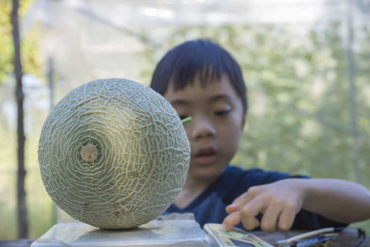 Close-up of boy weighing muskmelon on machine outdoors