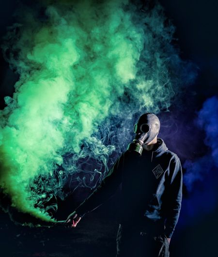 Man wearing gas mask while holding green distress flare at night