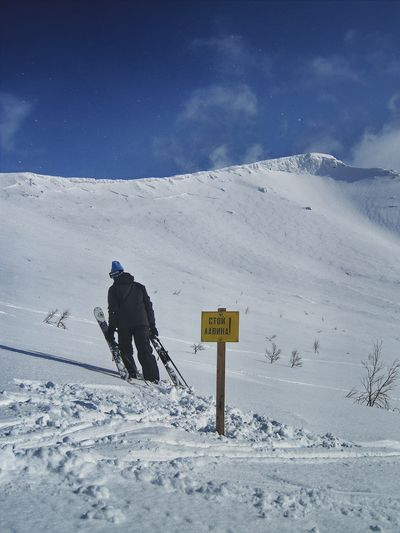 Man Preparing For Snowboarding On Snowcapped Mountains
