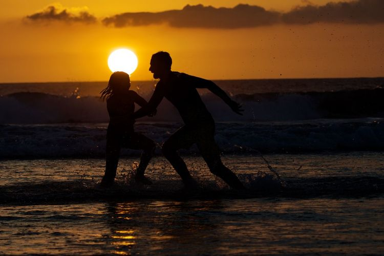 Water Sunset Sky Sea Two People Togetherness Land Orange Color Beauty In Nature Beach Silhouette Leisure Activity Men Real People Nature Lifestyles Bonding Sun Scenics - Nature Horizon Over Water Positive Emotion Couple - Relationship Outdoors