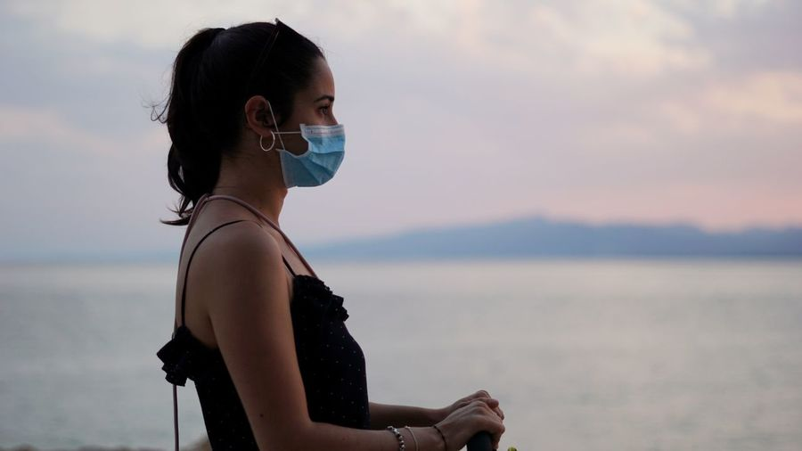 Portrait of woman with mask  against sea at sunset
