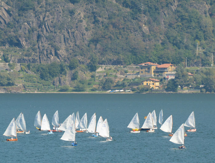 Sailboats sailing in sea against mountains
