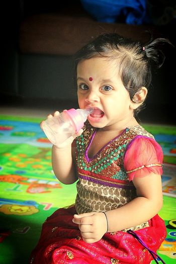 Portrait of cute baby girl drinking water from milk bottle at home