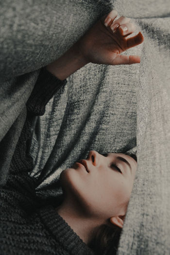 Close-up of woman under blanket