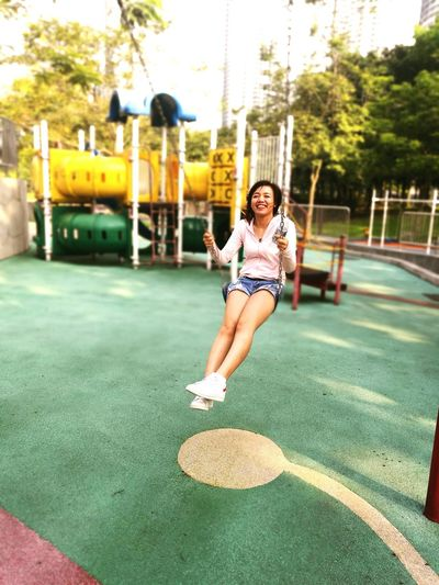 Young woman swinging at playground