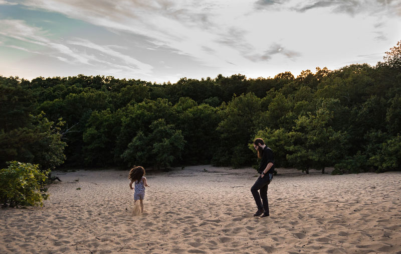 Full length of father with daughter at sandy beach