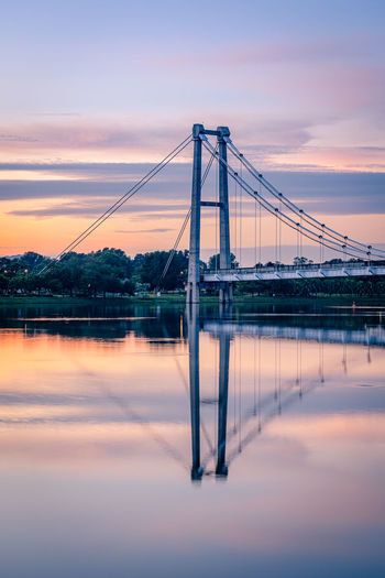 Suspension bridge over river against sky during sunset