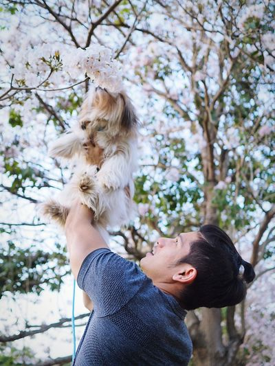 Young holding up dog outdoors