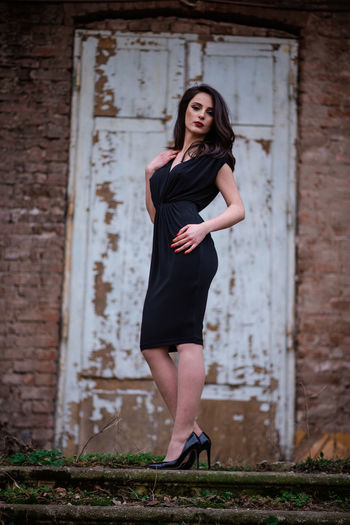 Full length portrait of woman standing against brick wall