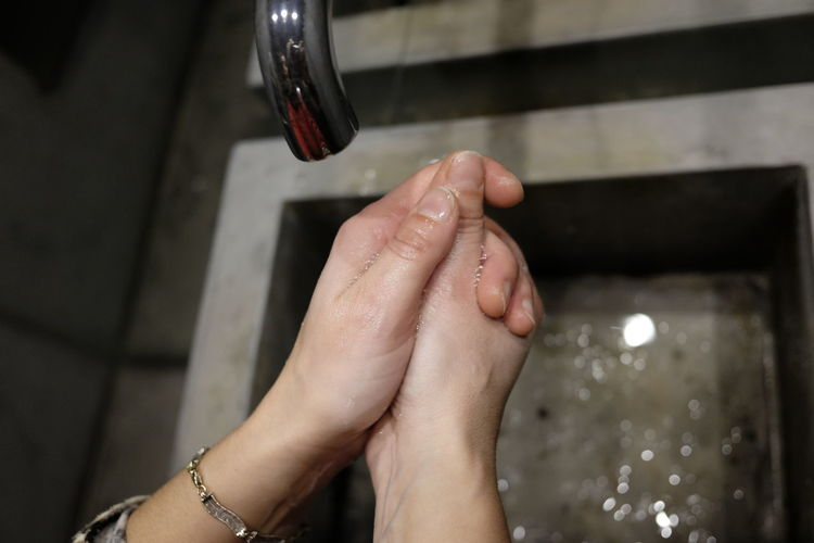 Cropped image of woman washing hands in sink at home