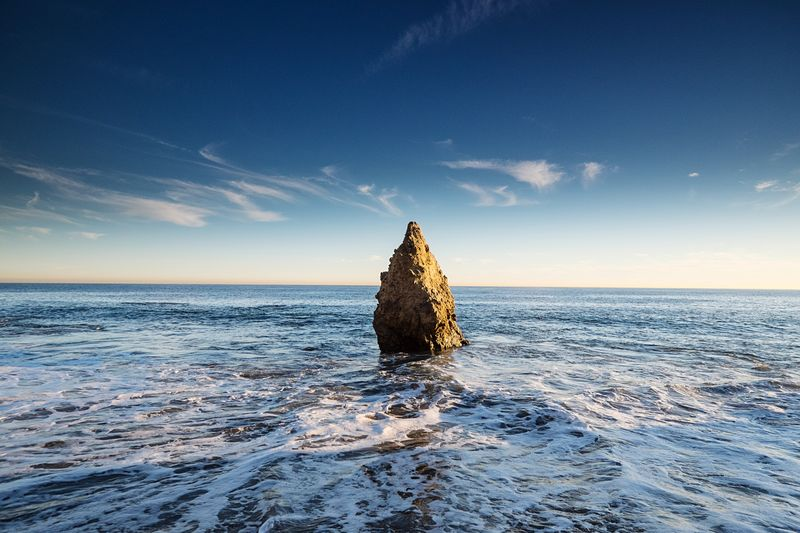 Stack rock in sea against blue sky