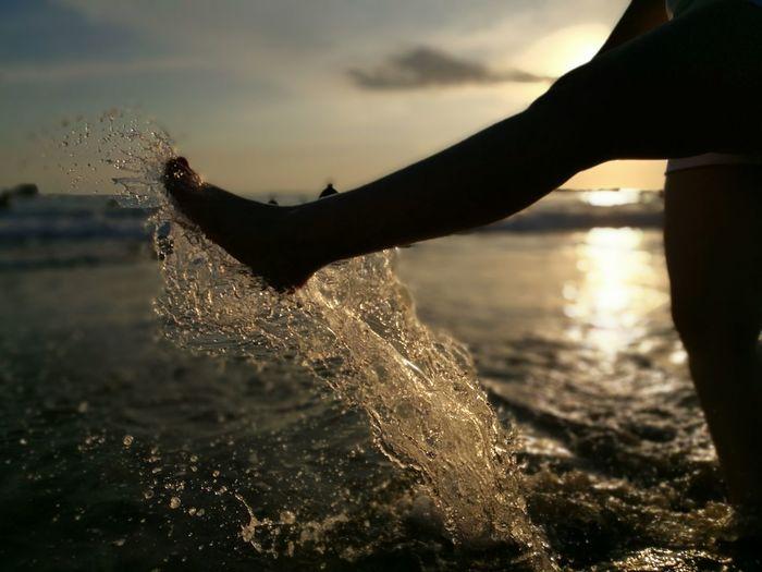 Close-Up Of Leg Splashing Water At Beach Against Sky